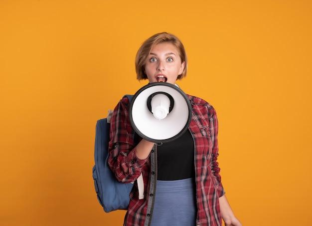 La giovane donna sorpresa dell'allievo con le cuffie che porta lo zaino parla nell'altoparlante isolato sulla parete arancione
