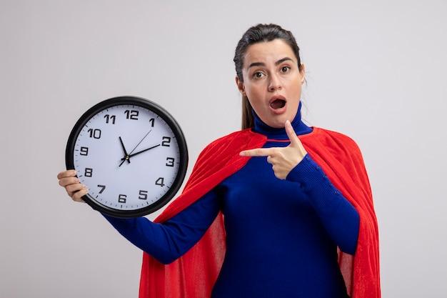 Удивленная молодая девушка супергероя держит и указывает на настенные часы, изолированные на белом фоне