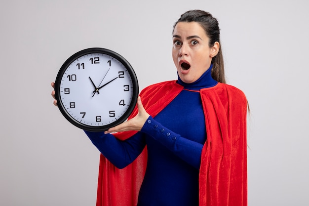 Удивленная молодая девушка супергероя, держащая настенные часы, изолированные на белом фоне