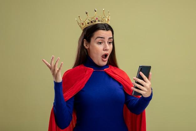 Ragazza giovane supereroe sorpresa che indossa la corona che tiene e che esamina la mano di diffusione del telefono isolata su fondo verde oliva