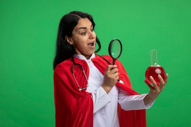 Удивленная молодая девушка-супергерой в медицинском халате со стетоскопом, держащая и смотрящая на химическую стеклянную бутылку, наполненную красной жидкостью, с лупой, изолированной на зеленом