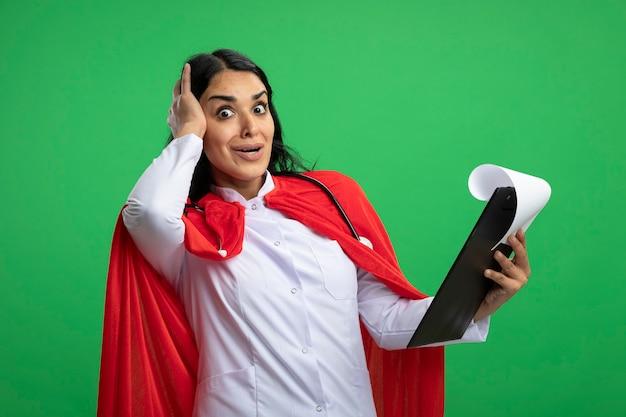 Giovane ragazza sorpresa del supereroe che porta veste medica con lo stetoscopio che tiene appunti mettendo la mano sulla testa isolata sul verde