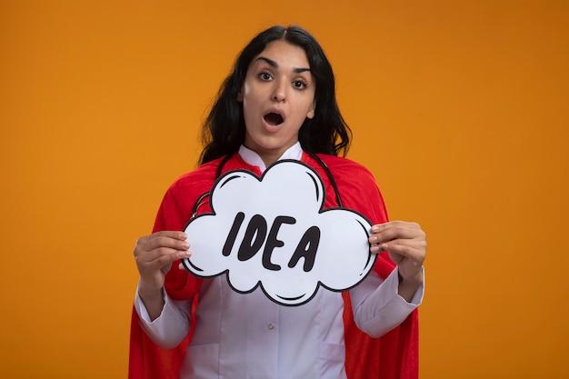Удивленная молодая девушка-супергерой в медицинском халате со стетоскопом, держащая пузырь идеи, изолированный на оранжевом