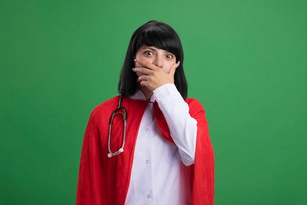 녹색 벽에 고립 된 손으로 의료 가운과 망토 덮여 입으로 청진기를 입고 놀란 젊은 슈퍼 히어로 소녀