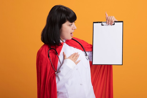 オレンジ色に分離された心臓に手を置いてクリップボードを保持し、医療ローブとマントと聴診器を身に着けている驚いた若いスーパーヒーローの女の子