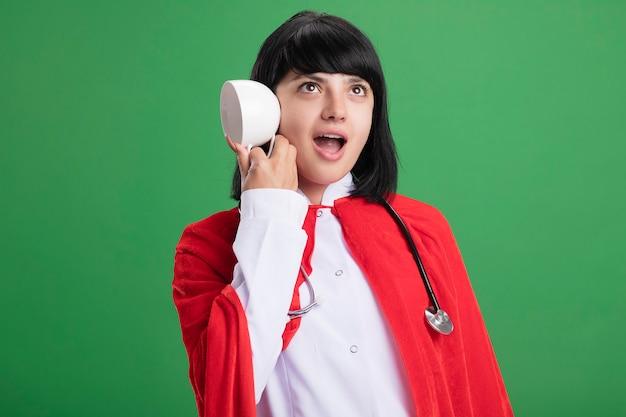 의료 가운과 녹색 벽에 고립 된 컵과 제스처를 듣고 보여주는 망토와 청진기를 입고 놀란 젊은 슈퍼 히어로 소녀
