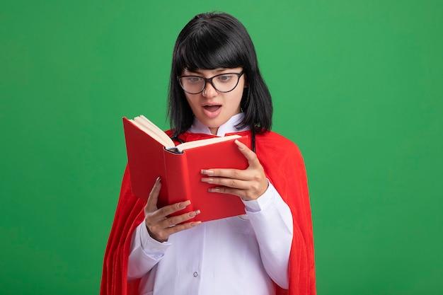 안경 들고 녹색에 고립 된 책을보고 의료 가운과 망토와 청진기를 입고 놀란 젊은 슈퍼 히어로 소녀