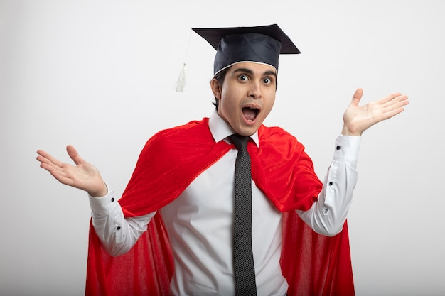 ネクタイと白い背景で隔離の手を広げて卒業帽子を身に着けているカメラを見て驚いた若いスーパーヒーローの男
