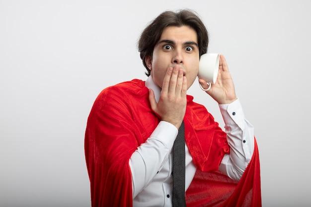 ネクタイを身に着けているカメラを見て驚いた若いスーパーヒーローの男は、白い背景で隔離の手でカップと覆われた口でジェスチャーを聞くを示しています