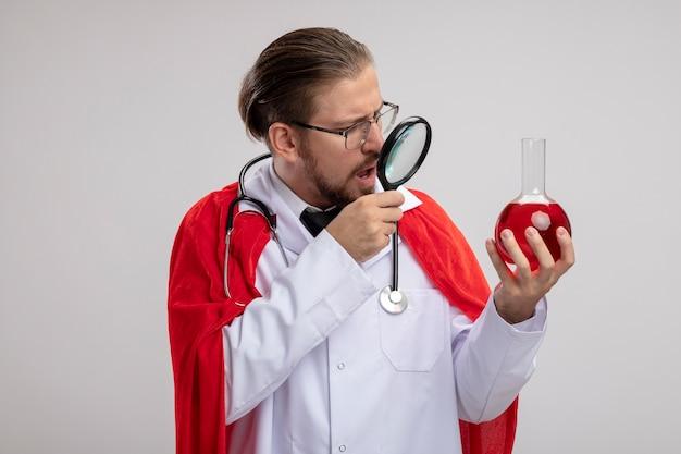 聴診器とガラスの医療ローブを身に着けている驚いた若いスーパーヒーローの男は、白い背景で隔離の拡大鏡と赤い液体で満たされた化学ガラス瓶を保持し、見て
