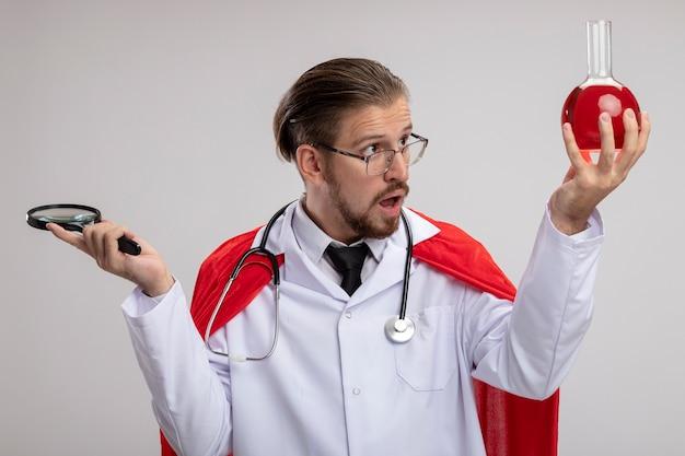 聴診器と拡大鏡を保持し、白い背景で隔離の彼の手で赤い液体で満たされた化学ガラス瓶を見て医療ローブを身に着けている驚いた若いスーパーヒーローの男