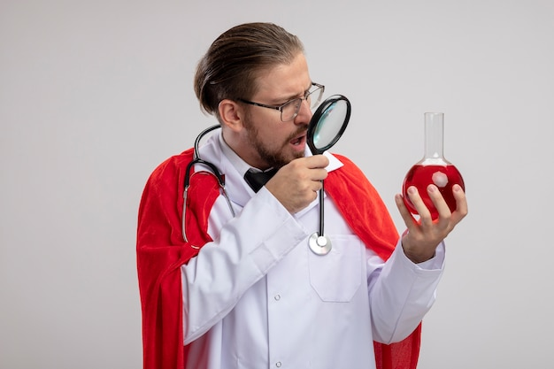 Surprised young superhero guy wearing medical robe with stethoscope and glasses holding and looking at chemistry glass bottle filled with red liquid with magnifier isolated on white background