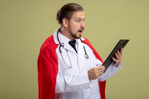 Удивленный молодой супергерой со стетоскопом в медицинском халате, держащий и смотрящий в буфер обмена, изолированный на оливково-зеленом фоне