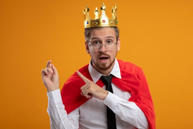 コピースペースでオレンジ色の背景に分離された後ろに眼鏡ポイントとネクタイと王冠を身に着けている驚いた若いスーパーヒーローの男