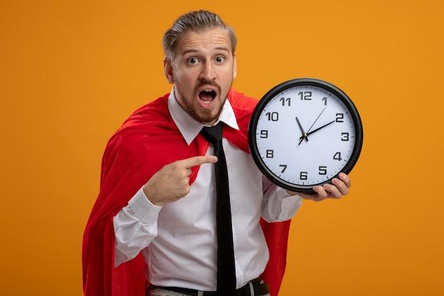 Удивленный молодой парень супергероя в галстуке держит и указывает на настенные часы, изолированные на оранжевом фоне