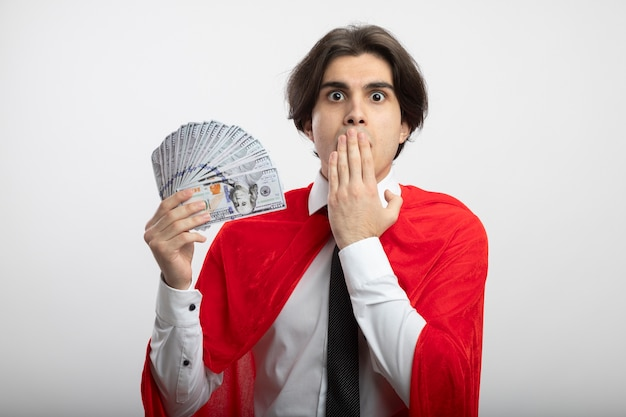 現金を保持し、手で口を覆ったネクタイを身に着けている驚いた若いスーパーヒーローの男