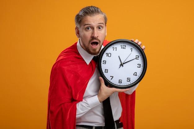 Удивленный молодой супергерой в галстуке, держащий настенные часы на оранжевом фоне