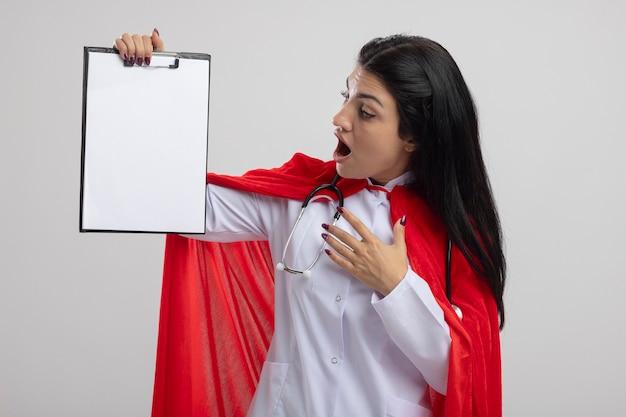 白い壁に隔離された空気中に手を保持し、クリップボードを保持し、聴診器を身に着けている驚いた若いスーパーウーマン