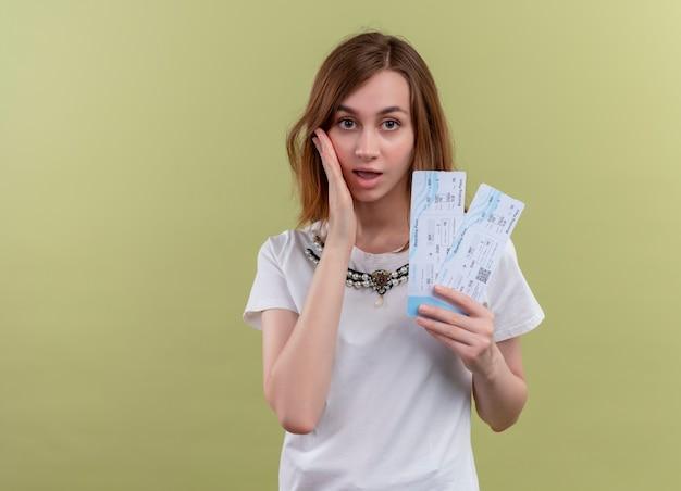 비행기 티켓을 들고 복사 공간이 격리 된 녹색 벽에 뺨에 손을 넣어 놀란 젊은 여행자 소녀