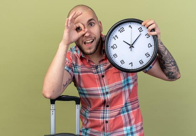 시계를 들고 복사 공간이 있는 올리브 녹색 벽에 격리된 손가락을 통해 앞을 바라보는 놀란 젊은 여행자