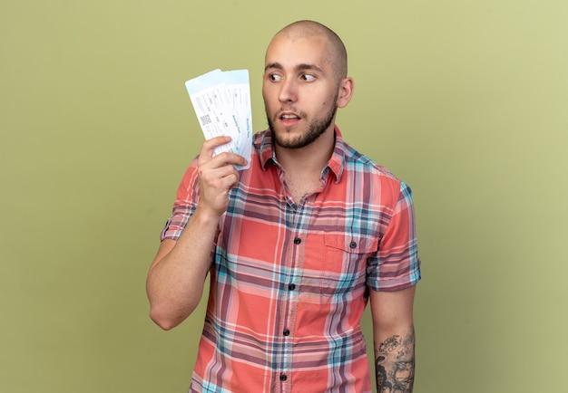 Sorpreso giovane viaggiatore uomo che tiene e guarda i biglietti aerei isolati sulla parete verde oliva con spazio di copia