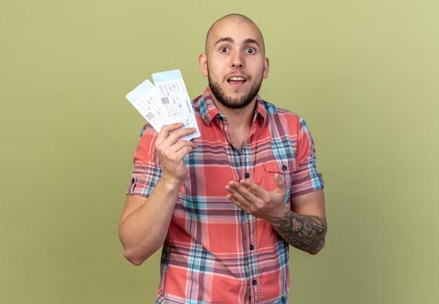 Sorpreso giovane viaggiatore uomo che tiene e indica i biglietti aerei isolati sulla parete verde oliva con spazio di copia