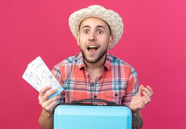 Sorpreso giovane viaggiatore con cappello da spiaggia di paglia in possesso di biglietti aerei in piedi dietro la valigia isolata sulla parete rosa con spazio di copia