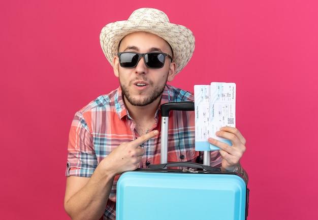 Sorpreso giovane viaggiatore con cappello da spiaggia di paglia in occhiali da sole che tiene e indica i biglietti aerei in piedi dietro la valigia isolata sulla parete rosa con spazio di copia