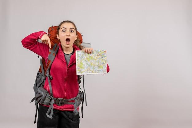 Giovane viaggiatore sorpreso con un grande zaino che tiene mappa su grigio isolato