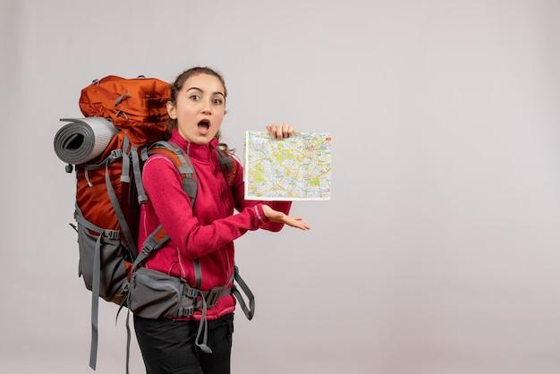 Удивленный молодой путешественник с большим красным рюкзаком, держащий карту на сером изолированном