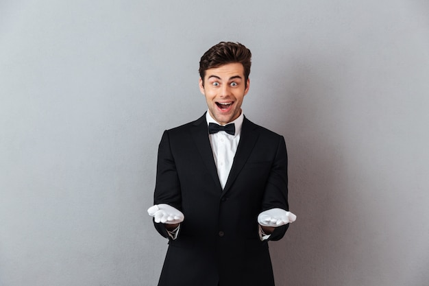 Surprised young waiter standing isolated