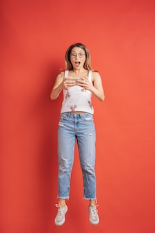 Surprised young woman always on mobile on red wall