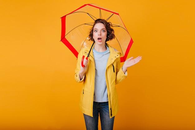 Giovane donna sorpresa in attrezzatura casuale di autunno che posa emotivamente con l'ombrello. ragazza riccia in piedi sotto l'ombrellone con stupore.