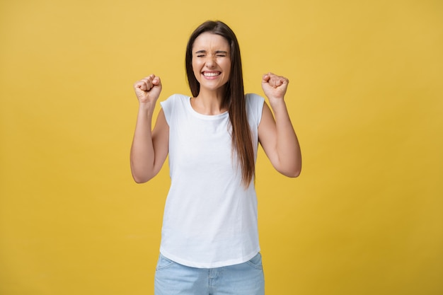 Surprised young woman in excited emotion over yellow background.