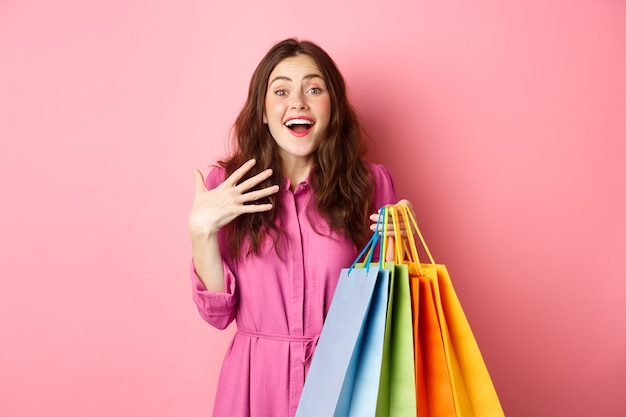 驚いた若い女性は驚いてあえぎ、胸に手をつないで、セール割引に驚いて笑い、買い物袋を持って、ピンクの壁に立っていました。