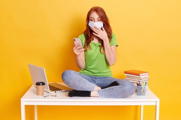 驚いた若い女性は、学びながら携帯電話を持ち、口を手のひらで覆い、医療用マスクとカジュアルな服を着て、組んだ足でテーブルに座っている間に、テキストメッセージでニュースを受け取りました。
