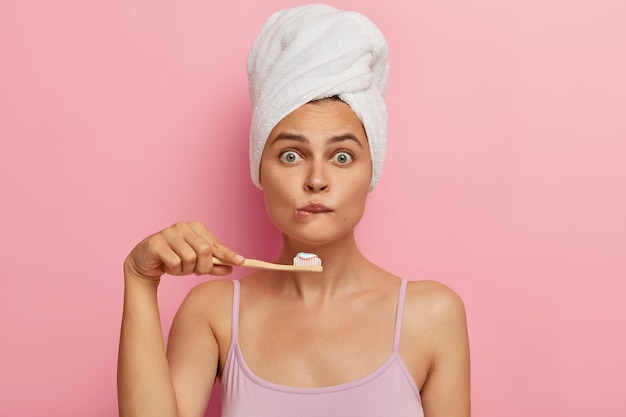 Surprised young woman has morning routine, shocked being short of time, bites lips, holds wooden toothbrush, brushes teeth, wears white towel on head, casual sleeveless shirt