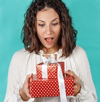 Удивленная молодая женщина, держащая в руках подарки, изолированные на зеленом