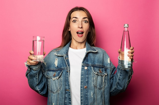 Surprised young woman holding glass with water and glass water bottle on pink surface