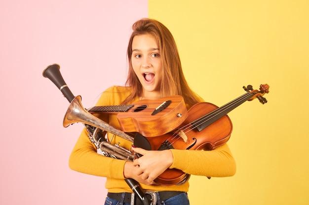 Удивленная молодая женщина, держащая музыкальные инструменты