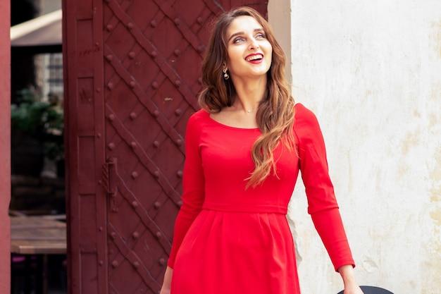 Удивленная молодая женщина в красном платье идет по улице города.