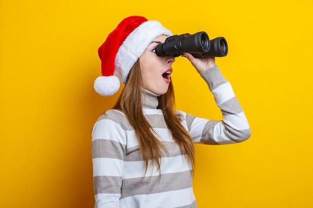 산타클로스 모자를 쓴 놀란 젊은 여성은 노란색 배경에 쌍안경을 통해 보인다.
