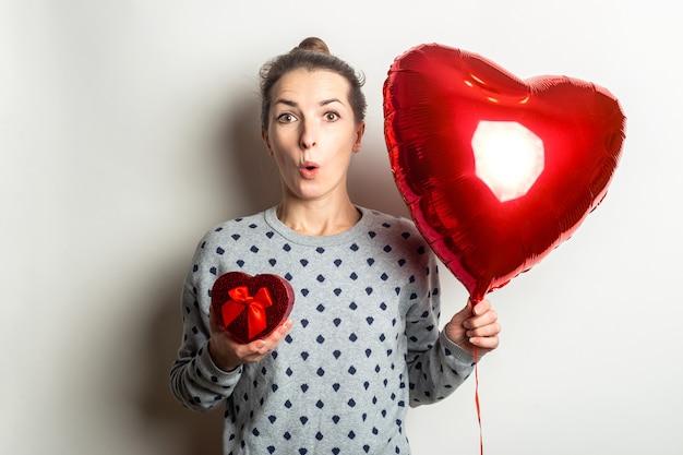 セーターを着た驚いた若い女性は、明るい背景に贈り物とハートの気球を持っています。バレンタインデーのコンセプト。バナー。