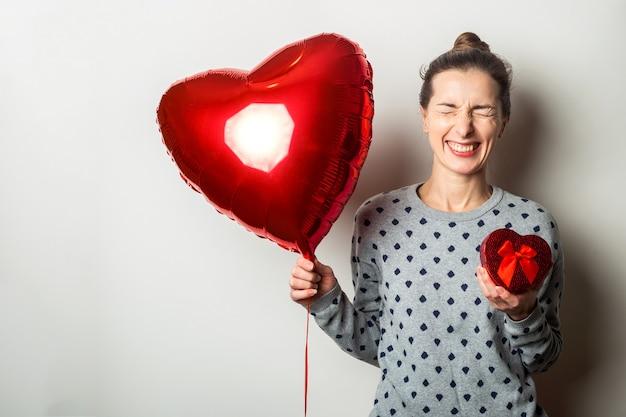 セーターを着た驚いた若い女性は、ハートの気球とハートの気球を持って、明るい背景の贈り物を喜んでいます。バレンタインデーのコンセプト。バナー。