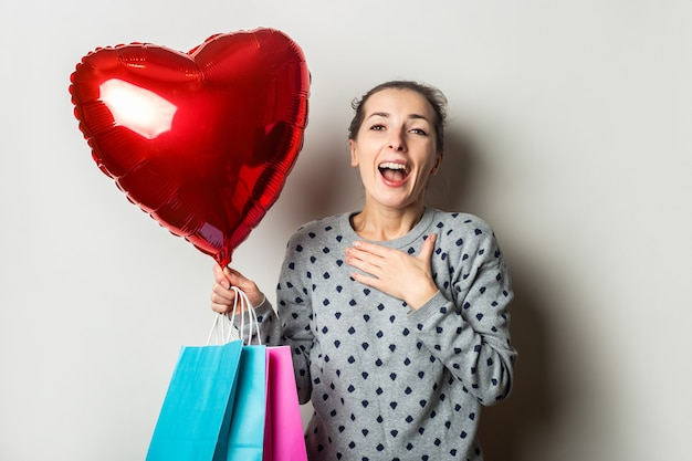 스웨터에 놀란 된 젊은 여자는 밝은 배경에 쇼핑 패키지와 심장 공기 풍선을 보유하고 있습니다. 발렌타인 데이 개념. 배너.