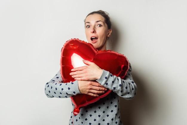 セーターを着た驚いた若い女性は、明るい背景に気球の心を抱きしめます。バレンタインデーのコンセプト。愛する人を探しましょう。