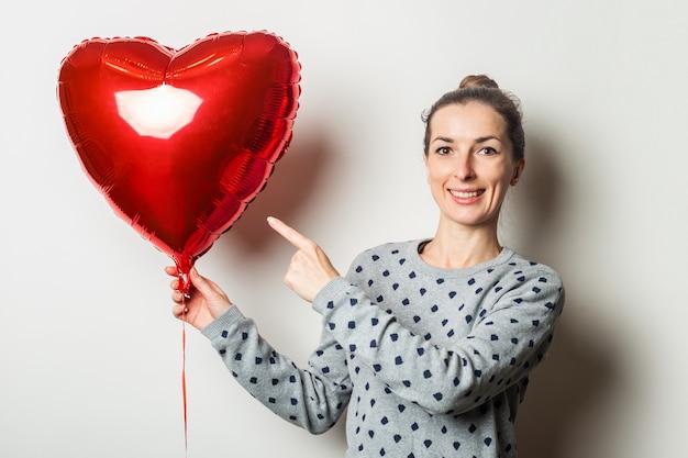 セーターを着た驚いた若い女性は、明るい背景の上の心臓の気球に指を向けます。バレンタインデーのコンセプト。愛する人を探しましょう。