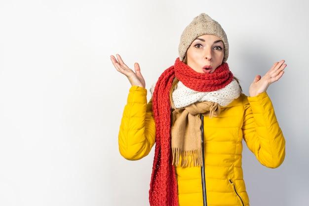 Удивленная молодая женщина в желтом пиджаке изолирована