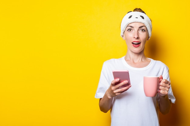 Удивленная молодая женщина в повязке с телефоном и чашкой кофе на желтом фоне