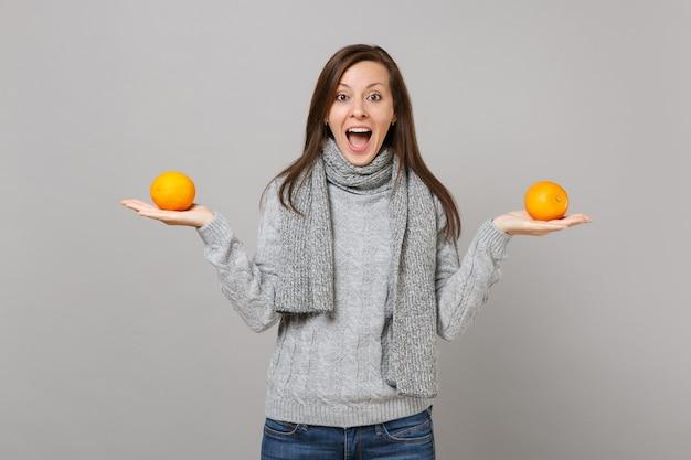 Удивленная молодая женщина в сером свитере, шарфе, держащем апельсины, изолированные на сером фоне, студийный портрет. здоровый образ жизни моды, искренние эмоции людей, концепция холодного сезона. копируйте пространство для копирования.